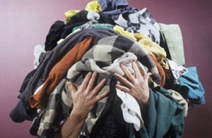 holding pile of old clothes